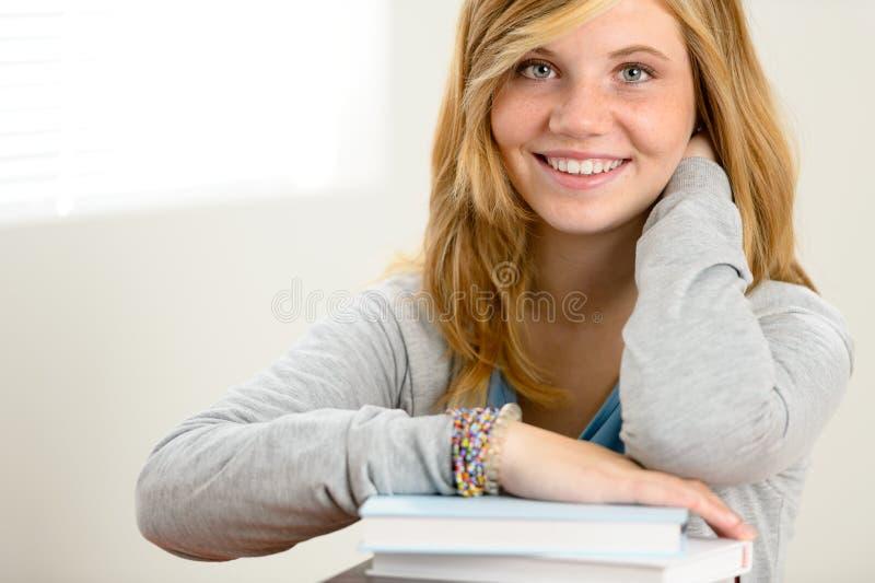 Lycklig studentflicka som lutar över böcker royaltyfri fotografi