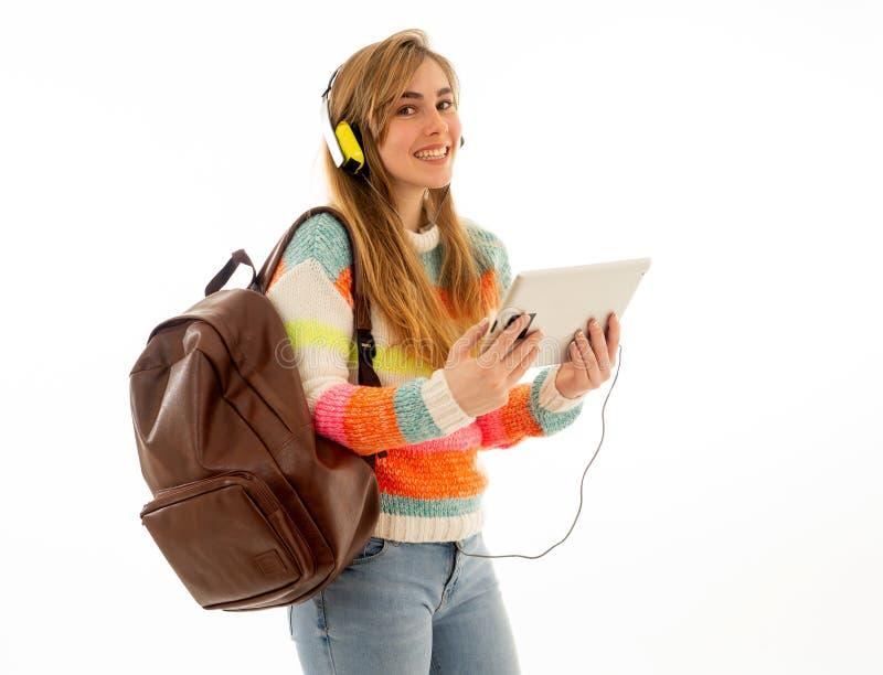 Lycklig studentkvinna i hörlurar som ser den digitala minnestavlan som lyssnar till musik eller den orubbliga videoen royaltyfria foton