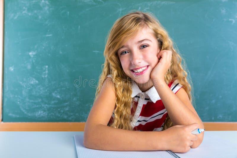 Lycklig studentuttrycksskolflicka i klassrum arkivbild