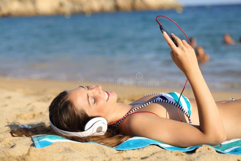 Lycklig sunbather som lyssnar till musik med den smarta telefonen royaltyfri foto