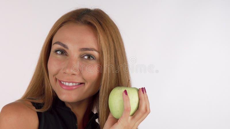 Lycklig sund härlig kvinna som glatt ler och att rymma ett äpple royaltyfri bild