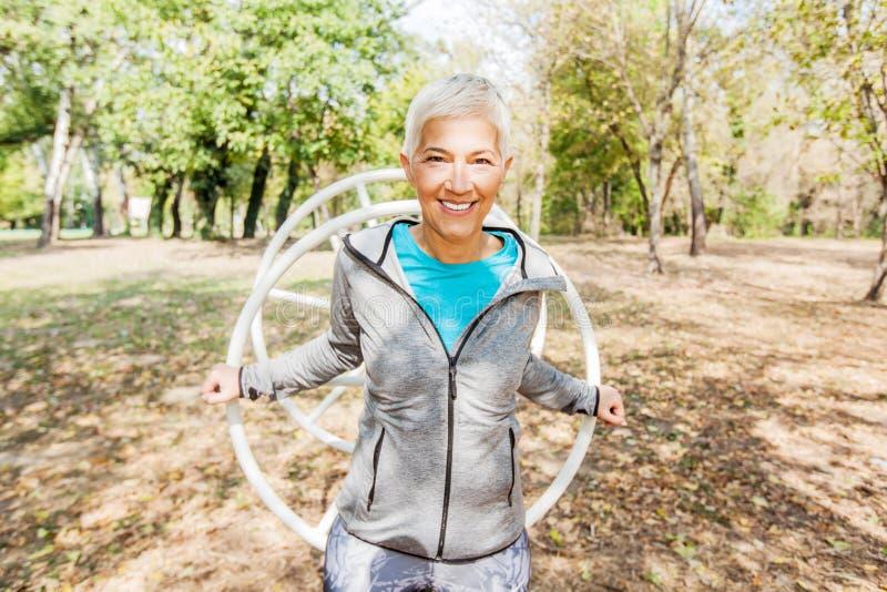 Lycklig sund hög kvinnagenomkörare på den utomhus- idrottshallen i natur arkivbilder