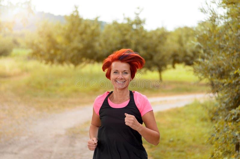 Lycklig sund kvinna som joggar längs utomhus- bana arkivfoto