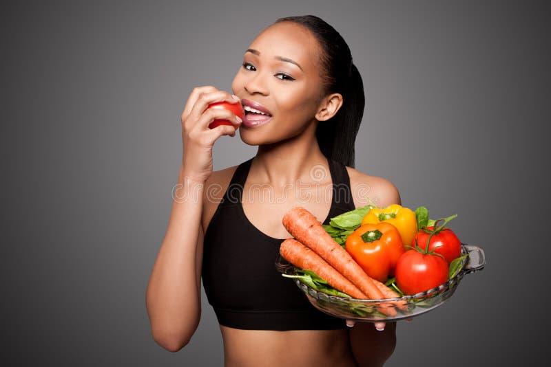 Lycklig sund svart asiatisk kvinna som äter grönsaker arkivbild