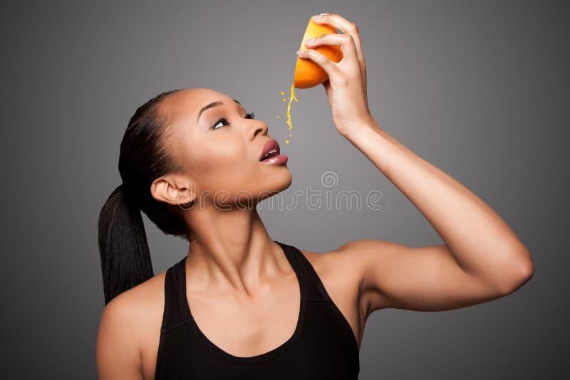 Lycklig sund svart asiatisk kvinna som pressar frukt för orange fruktsaft royaltyfria bilder