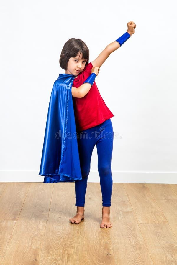 Lycklig superhero som har gyckel för flickamakt och feminismbegrepp arkivfoton