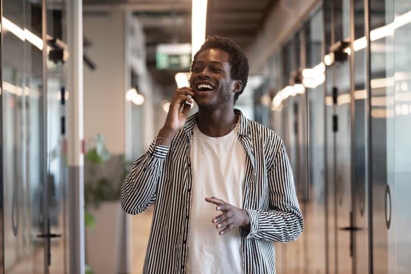 Lycklig svart affärsman som talar på telefonen som i regeringsställning står hallet royaltyfri foto