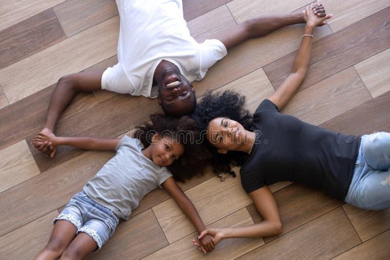 Lycklig svart familj som ligger på det varma trägolvet som rymmer händer arkivfoto