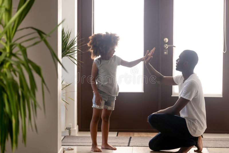 Lycklig svart farsa och litet ge sig för dotter som är höga-fem i hall royaltyfria bilder