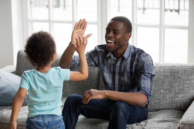 Lycklig svart farsa och son som ger högt-fem spela hemma royaltyfri bild