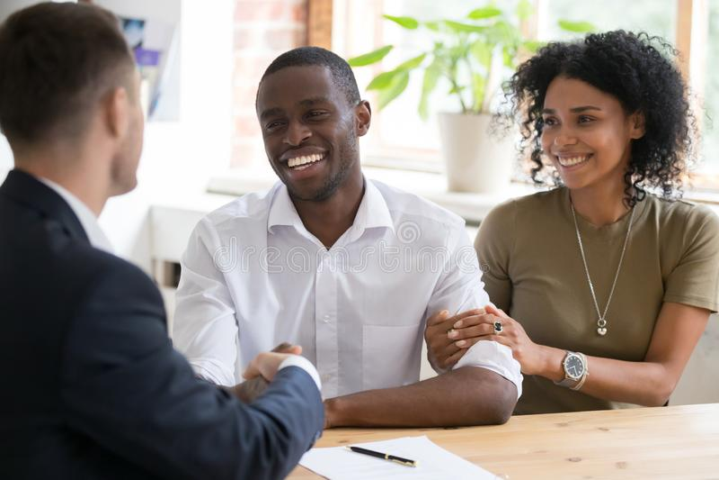 Lycklig svart hyresvärd för försäkringsgivare för parhandshakingfastighetsmäklare på möte arkivfoton