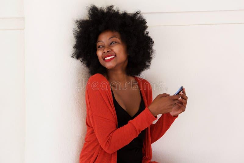 Lycklig svart kvinna med den smarta telefonen vid den vita väggen royaltyfria bilder