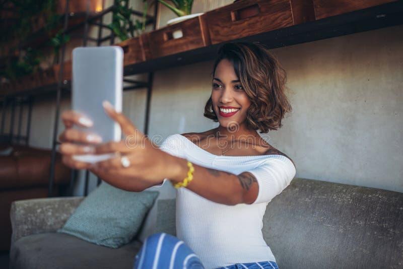 Lycklig svart kvinna som använder digitala minnestavlor, medan sitta i modernt kafé royaltyfria bilder