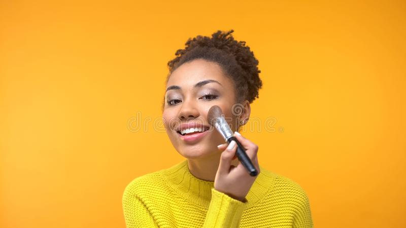 Lycklig svart kvinna som applicerar rodnaden, ung dam som förbereder sig för datumnärbilden, stil royaltyfria foton