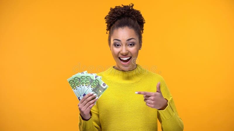 Lycklig svart kvinnlig som pekar p? eurosedlar i handen, finansiell framg?ng, l?n fotografering för bildbyråer