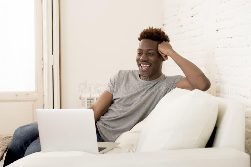 Lycklig svart man som sitter den hemmastadda soffasoffan som arbetar eller tycker om internetfilm i bärbar dator royaltyfri bild