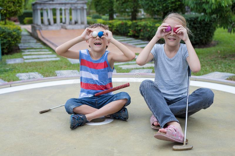 Lycklig syskongrupp som spelar mini- golf royaltyfri fotografi