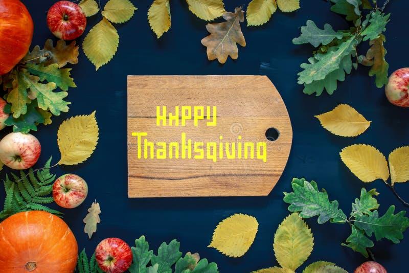 Lycklig tacksägelsetext med pumpor och sidor över mörk wood bakgrund royaltyfri foto