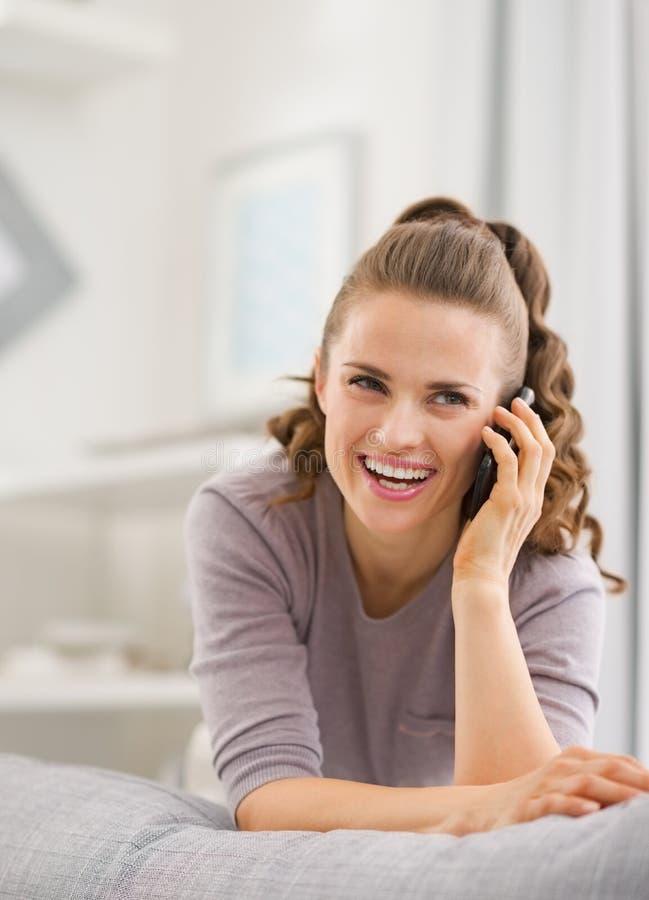 Lycklig talande mobiltelefon för ung kvinna i vardagsrum arkivbilder