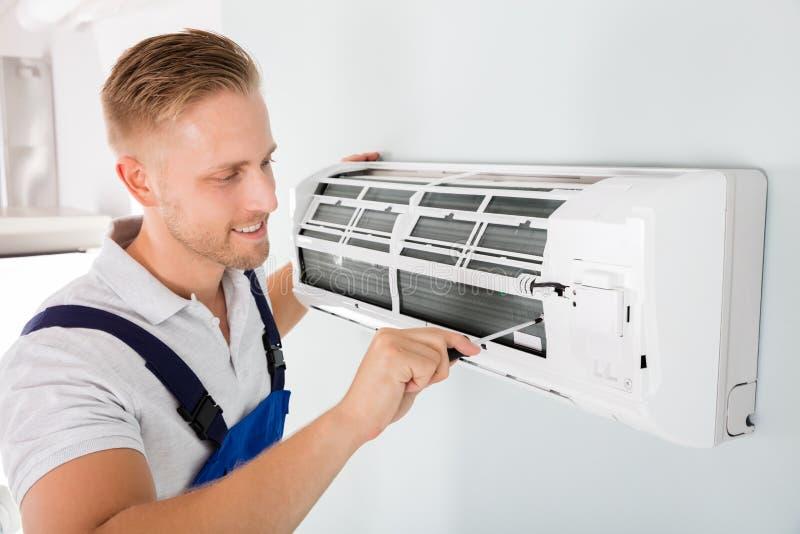 Lycklig tekniker Repairing Air Conditioner royaltyfri bild