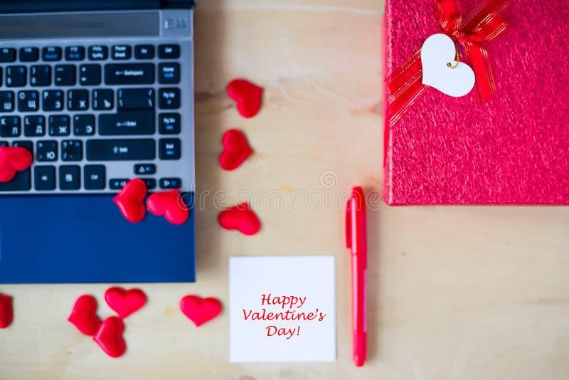 Lycklig text för dagen för valentin` som s var skriftlig på vita klistermärkear, PC:n, den röda pennan, gåvaask, dekorerade vid r arkivfoton