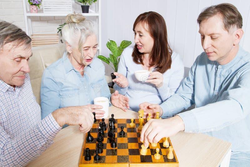 Lycklig tid för familjschacklek på vårdhemmet för åldring Föräldrar med barn har roligt samtal och fritid Pensionären kopplar iho arkivfoton