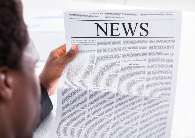 lycklig tidningsavläsning för affärsman royaltyfri foto