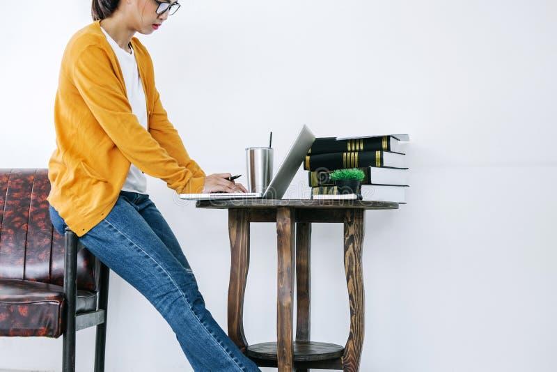 Lycklig tillfällig ung asiatisk kvinna som arbetar i hem- eller litet kontor w royaltyfri bild