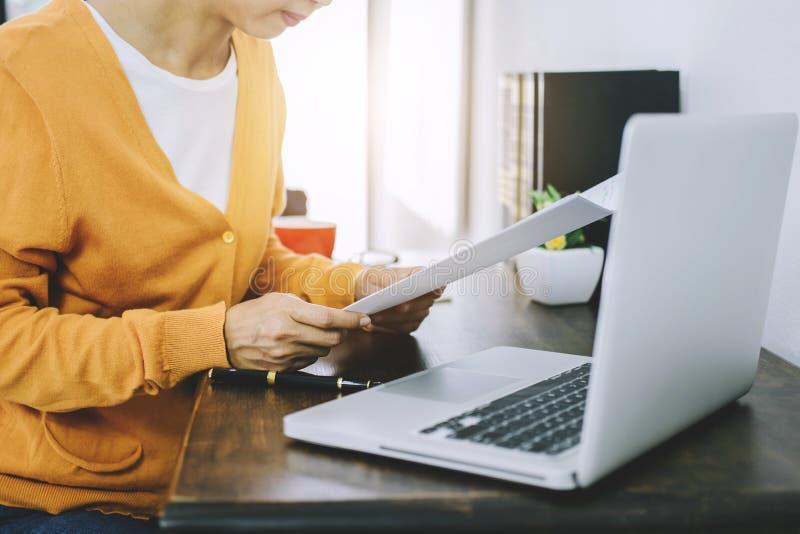 Lycklig tillfällig ung asiatisk kvinna som arbetar i hem- eller litet kontor w arkivbilder