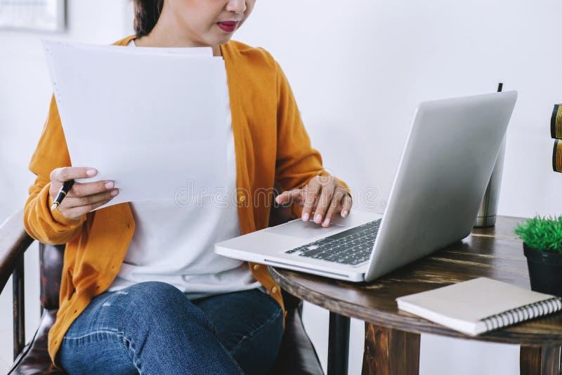 Lycklig tillfällig ung asiatisk kvinna som arbetar i hem- eller litet kontor w arkivbild