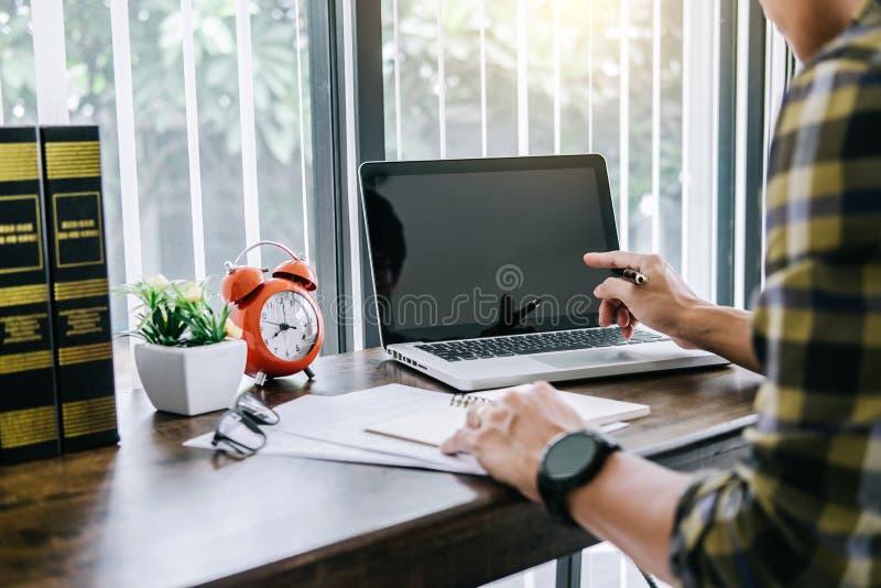 Lycklig tillfällig ung asiatisk man som arbetar i hem- eller liten kontorsintelligens royaltyfri foto