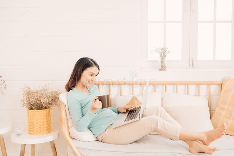 Lycklig tillf?llig h?rlig kvinna som arbetar p? ett b?rbar datorsammantr?de p? soffan i huset royaltyfria foton