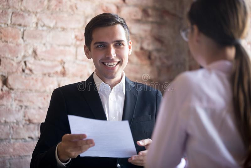 Lycklig timme-chef med meritförteckningen som ser den kvinnliga jobbsökaren arkivbild