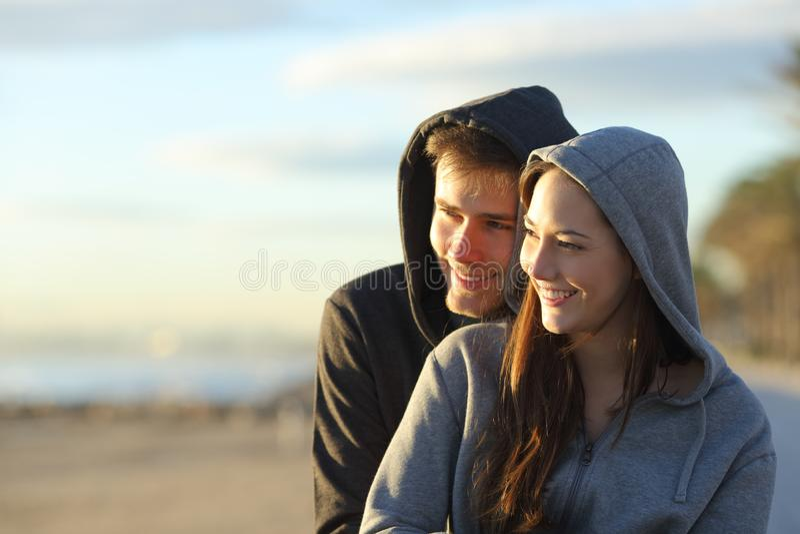 Lycklig tonår som beskådar solnedgång på stranden royaltyfria bilder