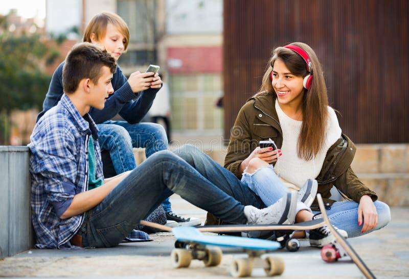 Lycklig tonår som spelar på smarthphones och lyssnar till musik royaltyfri bild