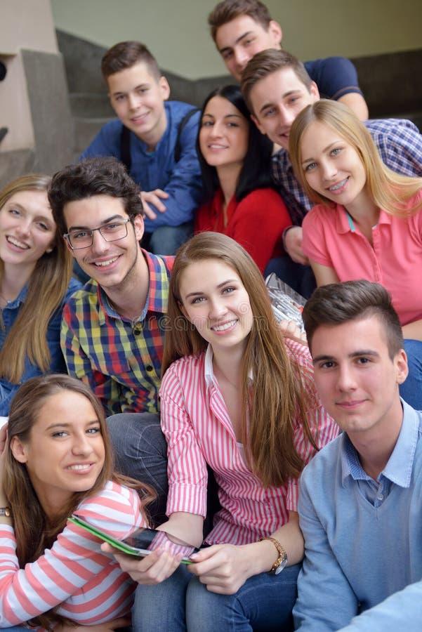 Lycklig tonårgrupp i skola arkivbild