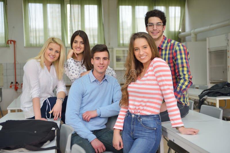 Lycklig tonårgrupp i skola royaltyfri bild