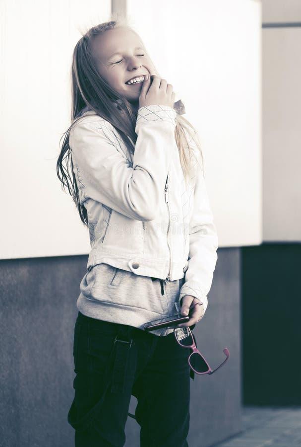 Lycklig tonårig flicka i det vita omslaget som skrattar i stadsgata arkivbild