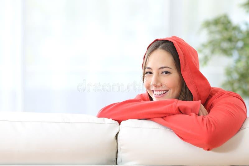 Lycklig tonårig flicka i rött posera hemma arkivbild