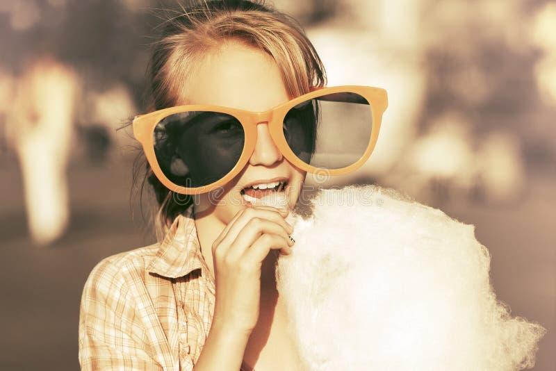 Lycklig tonårig flicka i solglasögon som äter sockervadden som går i gata arkivfoton