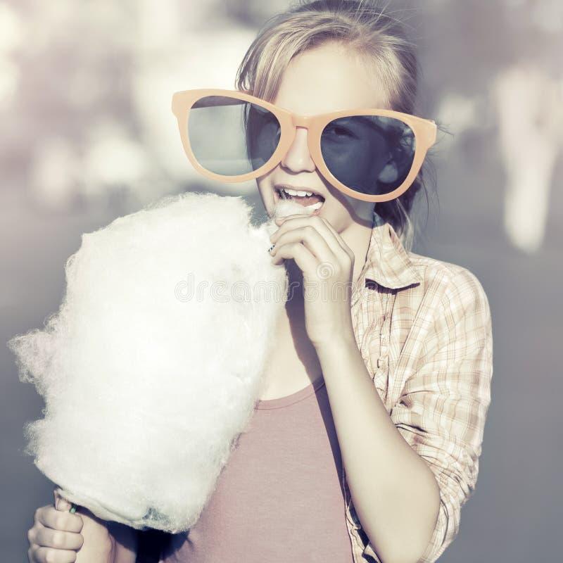 Lycklig tonårig flicka i solglasögon som äter sockervadden arkivfoto