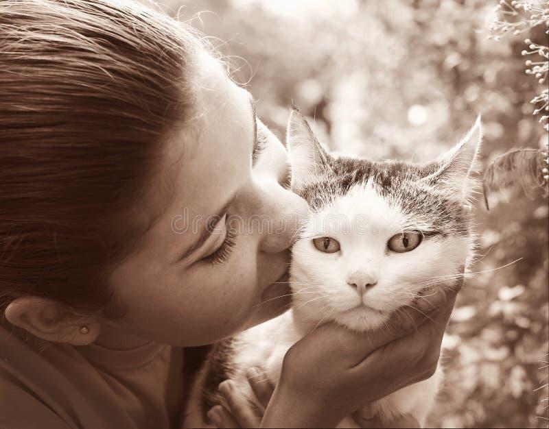 Lycklig tonårig flicka med kattslut upp den svartvita ståenden för sepia på sommarträdgårdbakgrund arkivfoton
