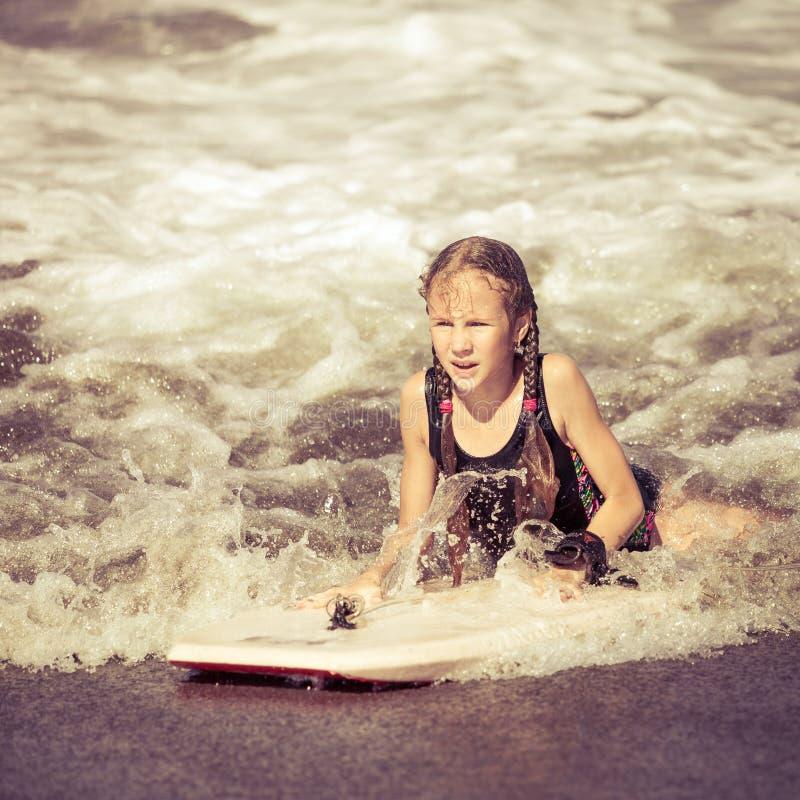 Lycklig tonårig flicka med surfingbrädan på stranden arkivfoto