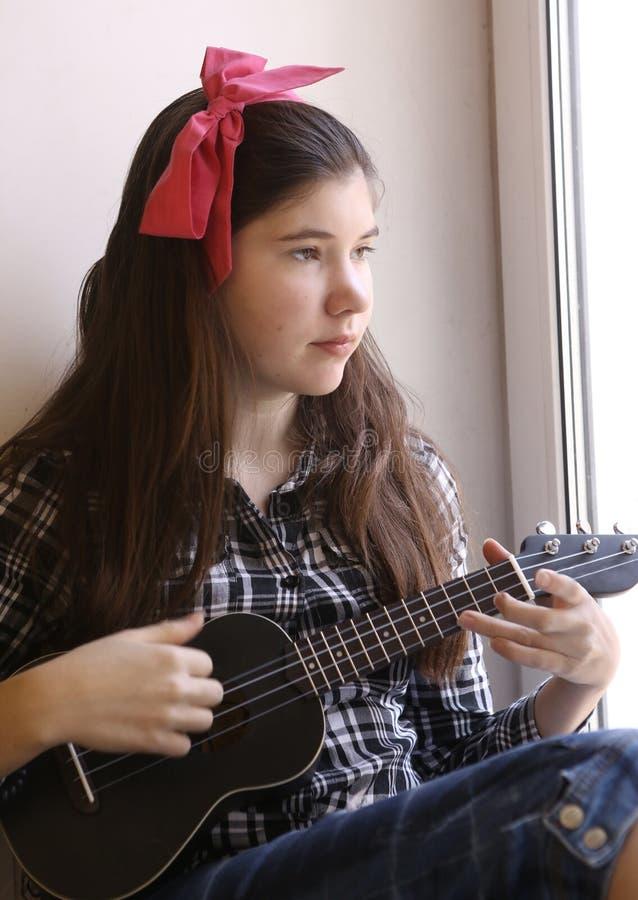 Lycklig tonårig flicka med ukulelegitarren i kontrollerad skjorta och jeans som spelar blick på fönstret royaltyfria foton