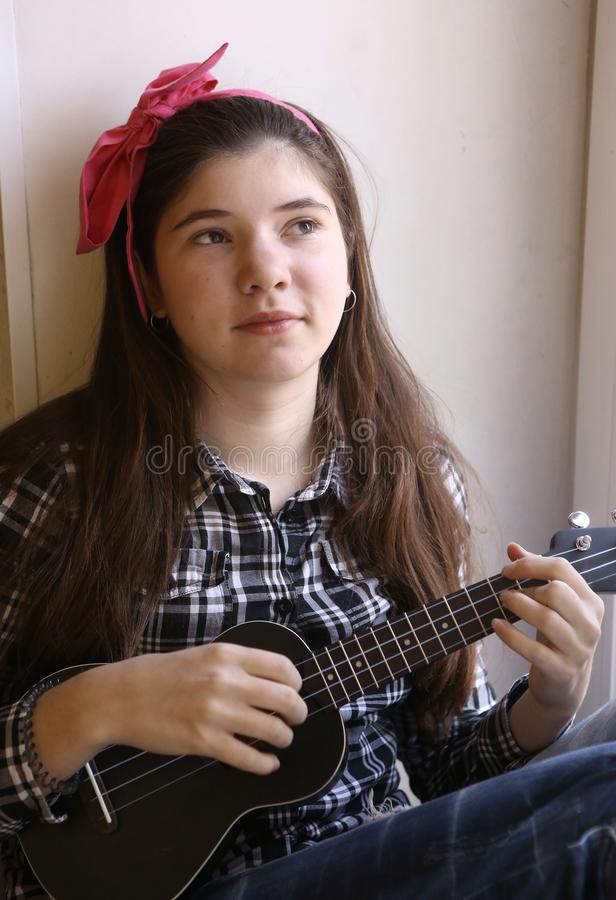Lycklig tonårig flicka med ukulelegitarren i kontrollerat spela för skjorta och för jeans fotografering för bildbyråer
