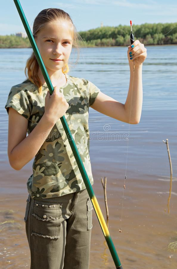 Lycklig tonårig flicka som förbereder sig till att fiska på floden arkivfoton
