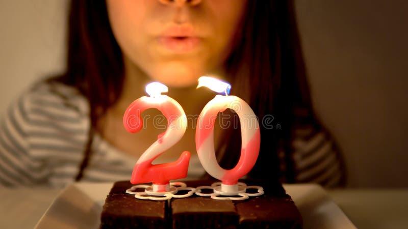 Lycklig tonårig flicka som firar hennes 20th födelsedag och blåser stearinljus royaltyfria bilder