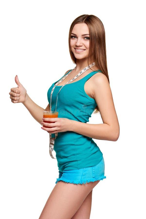 Lycklig tonårig flicka som rymmer ett exponeringsglas av morotfruktsaft royaltyfri foto