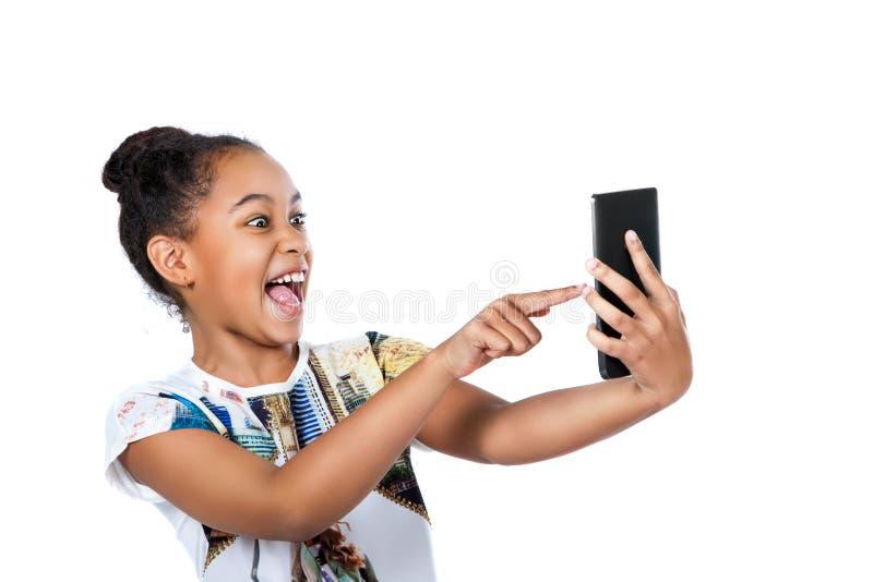 Lycklig tonårig flicka som ser skärmen av minnestavlan royaltyfria foton