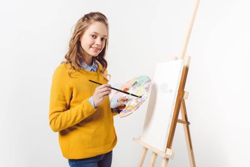 lycklig tonårig kvinnlig målare i gul tröja med målarfärgborsten och palett nära staffli med tom kanfas royaltyfri foto